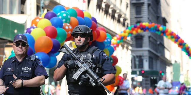 Police officers walk along the street near the parade route of the New York City Pride Parade on Sunday, June 26, 2016, in New York City. (AP Photo/Mel Evans)