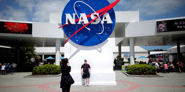 April 14, 2010: Tourists take pictures of a NASA sign at the Kennedy Space Center visitors complex in Cape Canaveral, Florida.