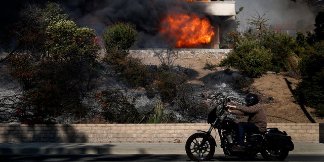 A man rides his bike past a home consumed by a wildfire.