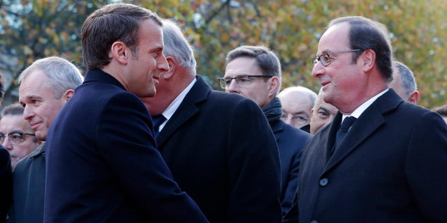 French President Emmanuel Macron, left, shakes hands with former French President Francois Hollande as they stand in front of a commemorative plaque outside the Stade de France stadium, in Saint-Denis, near Paris, Monday, Nov. 13, 2017.