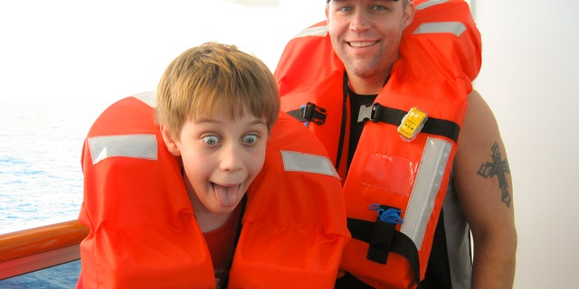 Father and his son put on life vests during cruise ship safety drill before departing.  Ocean in background. Son makes silly face just as mom snaps the vacation photo.