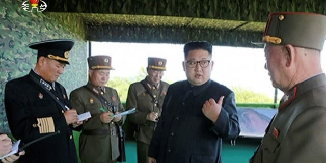 """This image made from video aired by North Korea's KRT on Saturday, Aug. 26, 2017, shows a photo of North Korean leader Kim Jong Un, second right, speaks with officials during what Korean Central News Agency called a """"target-striking contest"""" at unknown location in North Korea. (KRT via AP Video)"""