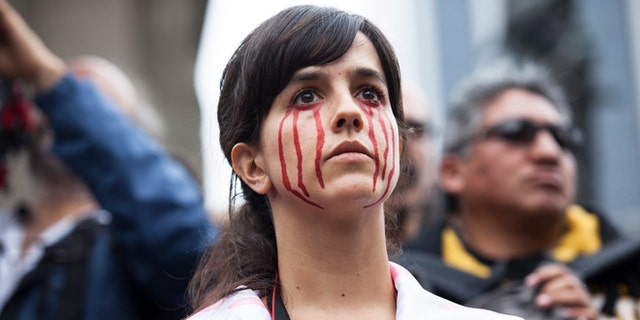 A young woman with fake blood painted on her face watches a protest for 43 missing students from Ayotzinapa Normal school in Mexico City, Mexico. (Photo by Brett Gundlock/Getty Images)