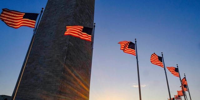 Tourists walk around the base of the Washington Monument on Presidents Day weekend as the sunsets Sunday, Feb. 19, 2017, in Washington. (AP Photo/J. David Ake)