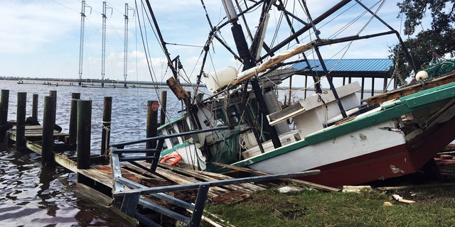 A shrimp boat is sunk at its mooring along the Pascagoula River in Moss Point, Miss., on Sunday, Oct. 8, 2017, after Hurricane Nate made landfall on Mississippi's Gulf Coast.