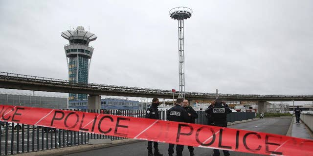 Police officers cordon off the access to the Orly airport, south of Paris, Saturday, March, 18, 2017. A man was shot to death Saturday after trying to seize the weapon of a soldier guarding Paris' Orly Airport, prompting a partial evacuation of the terminal, police said. Authorities warned visitors to avoid the area while an ongoing police operation was underway. (AP Photo/Thibault Camus)