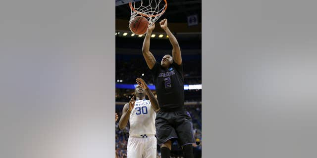 Kansas State's Marcus Foster (2) gets past Kentucky's Julius Randle (30) to dunk the ball during the first half of a second-round game in the NCAA college basketball tournament, Friday, March 21, 2014, in St. Louis. (AP Photo/Charlie Riedel)