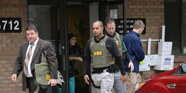 FBI agents leave the office of Dr. Fakhruddin Attar at the Burhani Clinic in Livonia, Mich., after completing a search for documents, April 21, 2017. The investigation was connected to the case of Dr. Jumana Nagarwala, who was charged with performing genital mutilation on two young girls from Minnesota. (Detroit News via AP)