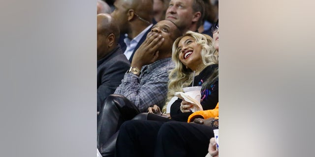 Jay-Z, left, and Beyonce look up at the scoreboard during an NBA basketball game between the Oklahoma City Thunder and the Los Angeles Clippers in Oklahoma City, Thursday, Nov. 21, 2013. (AP Photo/Sue Ogrocki)