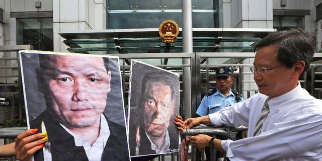 FILE - In this May 14, 2014 file photo, anti-Beijing protesters, holding pictures of human rights lawyer Pu Zhiqiang, protest outside the Chinese liaison office to demand Pu's release, in Hong Kong. Pu, a prominent Chinese rights lawyer whose trial is drawing near on charges of inciting ethnic hatred and provoking trouble has been denied access to lawyers for nearly a month, his wife and one of his attorneys said Monday, July 20, 2015. (AP Photo/Kin Cheung, File)