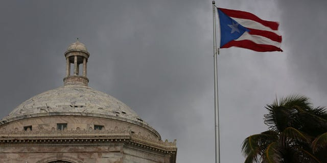 SAN JUAN, PUERTO RICO - JULY 01:  The Puerto Rican flag flies near the Capitol building as the island's residents deal with the government's $72 billion debt on July 1, 2015 in San Juan, Puerto Rico. Governor of Puerto Rico Alejandro Garc?a Padilla said in a speech recently that the people of Puerto Rico will have to make sacrifices and share the responsibilities to help pull the island out of debt. (Photo by Joe Raedle/Getty Images)