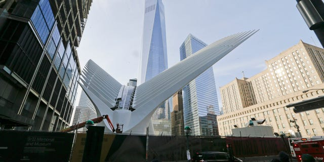 Pedestrians walk past the Oculus near World Trade Center Thursday, March 3, 2016, in New York. New Yorkers and tourists get their first look inside the cathedral-like hall that sits atop the new $4 billion train station at the World Trade Center. (AP Photo/Frank Franklin II)