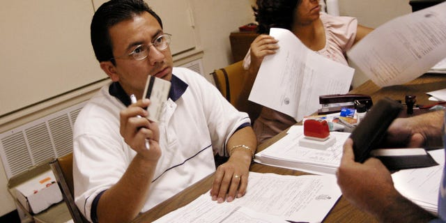LONGVIEW, TX - JULY 24:  Salvador Alanis (L), a Mexican Consulate official, asks to see proper Mexican and American identifications documents from an Mexican citizen applying for the ?Matricula Consular? card, at the Wesley-McCabe United Methodist Church July 24, 2004 in Longview, Texas. The identification card  is issued to Mexican citizens living outside of Mexico to recognize legitimate Mexicans in the U.S. Mexican Consulate officials from Dallas, Texas established what they called a ?mobile consulate? in Longview to process applicants from 450 Mexican citizens.  (Photo by Mario Villafuerte/Getty Images)