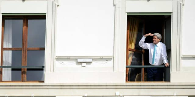 FILE - In this April 1, 2015 file photo US Secretary of State John Kerry looks at the view of Lake Geneva from his hotel room as the Iran nuclear talks continue in Lausanne, Switzerland. Iran left the negotiating table in Lausanne, Switzerland, on Thursday, Aoril 2, 2015 with a commitment to implement the Additional Protocol, IAEA's most potent monitoring instrument. (AP Photo/Keystone, Laurent Gillieron, file)