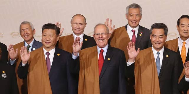 From left, Philippines's Secretary of Department of Foreign Affairs Perfecto Yasay, China's President Xi Jinping, Russia's President Vladimir Putin, Peru's President Pedro Kuczynski, Singapore's Prime Minister Lee Hsien Loong, Hong Kong's Chief Executive Leung Chun-ying and Taiwan 's special APEC envoy James Soong wave during the group photo at the annual Asia Pacific Economic Cooperation, APEC, summit in Lima, Peru, Sunday, Nov. 20, 2016. (AP Photo/Martin Mejia)