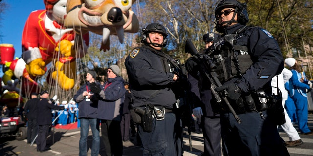 Heavily-armed members of the New York Police Department take a position along the route before the start of the Macy's Thanksgiving Day Parade in New York, Thursday, Nov. 23, 2017.