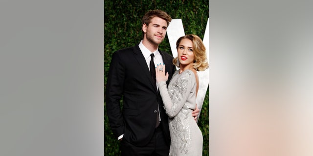 February 26, 2012. Singer Miley Cyrus (R) and actor Liam Hemsworth pose as they arrive at the 2012 Vanity Fair Oscar party in West Hollywood, California.