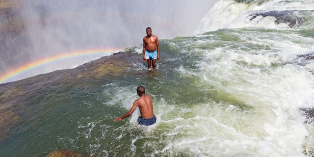 BXDT97 Man jumps into Devil's Pool at Victoria Falls.