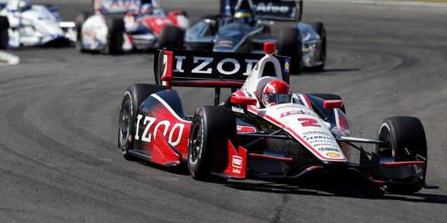 A.J. Allmendinger (2) leads a pack of cars into Turn 17 during the IndyCar Series Grand Prix of Alabama auto race in Birmingham, Ala., Sunday, April 7, 2013. (AP Photo/Butch Dill)
