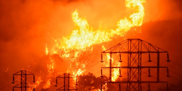 In this Saturday, Dec. 16, 2017, photo provided by the Santa Barbara County Fire Department, flames burn near power lines in Sycamore Canyon near West Mountain Drive in Montecito, Calif.