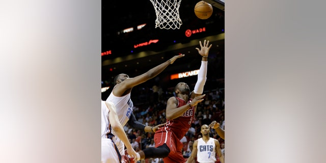 Miami Heat's Dwyane Wade (3) shoots over Charlotte Bobcats' Al Jefferson, left, during the first half of an NBA basketball game Sunday, Dec. 1, 2013, in Miami. (AP Photo/Lynne Sladky)