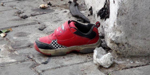 The shoe of a young victim and a piece of metal lay near the scene just hours after Saturday's bomb attack in Gaziantep, Turkey.