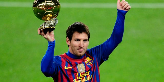 Lionel Messi, from Argentina, holds the Golden Ball award as European Footballer of the Year before a Spanish La Liga soccer match between FC Barcelona and Betis at the Camp Nou stadium in Barcelona, Spain, Sunday, Jan. 15, 2012. (AP Photo/Manu Fernandez)