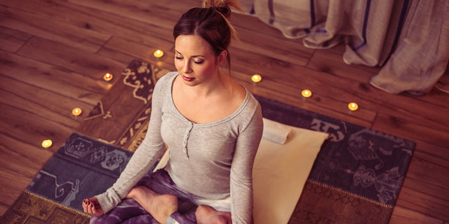 Adult caucasian woman practicing yoga exercise at home. Soft light, candles, brick wall in background
