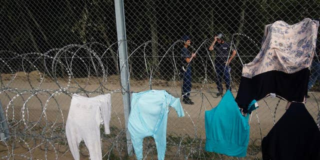 Clothes are placed on a fence to dry at the Horgos border crossing into Hungary, near Horgos, Serbia, Wednesday, Sept. 16, 2015. Small groups of migrants continued to sneak into Hungary on Wednesday, a day after the country sealed its border with Serbia and began arresting people trying to breach the razor-wire barrier, while a first group arrived in Croatia seeking another way into the European Union. (AP Photo/Darko Vojinovic)