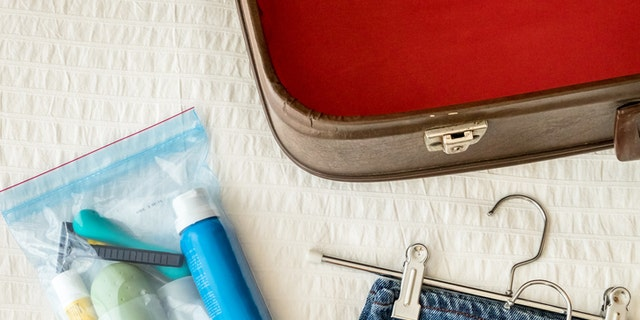 Open suitcase, trousers with hanger and liquid products in bag to transport in the cockpit of an airplane. Preparing travel luggage on the bed in the room.