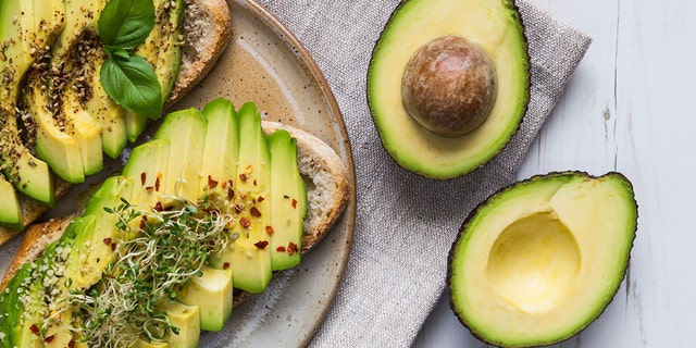 Toast with sliced avocado topping, basil leaf and seasoning.