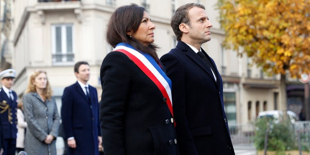 French President Emmanuel Macron and Paris mayor Anne Hidalgo, left, stand in front of a commemorative plaque facing the 'Le Carillon' bar and 'Le Petit Cambodge' restaurant during a ceremony marking the second anniversary of the Paris attacks, Monday Nov.13 2017