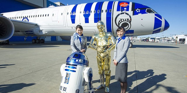 """Flight attendants pose in front of the aircraft with R2-D2 and C-3PO from """"Star Wars."""""""