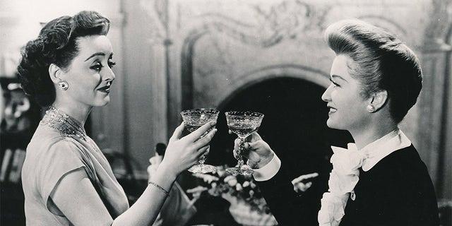 "Miriam Hopkins (right) toasting Bette Davis in the final scene of 1943's ""Old Acquaintance""."