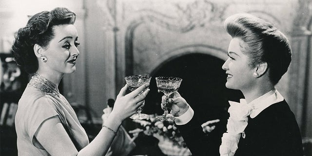 "Miriam Hopkins (right) toasting Bette Davis in the final scene of 1943's ""Old Acquaintance""."