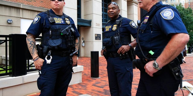 Security personnel from the Department of Homeland Security's Federal Protective Service, watch the vicinity around the Alexandria Federal Court in Alexandria, Va., on day one of Paul Manafort's trial, Tuesday, July 31, 2018.