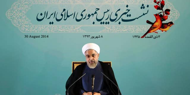 """Iranian President Hassan Rouhani gives a press conference in Tehran, Iran, Saturday, Aug. 30, 2014.  Rouhani called Western sanctions an """"invasion"""" on Saturday after Washington imposed existing sanctions on more than 25 businesses, banks and individuals suspected of working to expand Iran's nuclear program, support terrorism and help Iran evade U.S. and international sanctions. Iran's state TV also said the move violated an interim agreement reached with world powers under which Western nations agreed to ease sanctions in exchange for Iran curbing its nuclear activities.  However, Friday's action did not constitute an expansion of the sanctions regime. (AP Photo/Ebrahim Noroozi)"""
