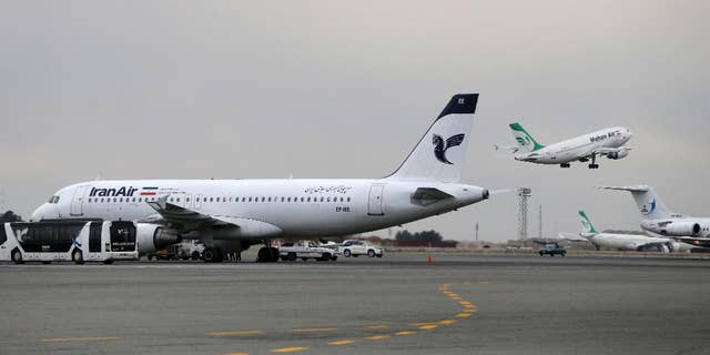 "In this photo taken on Feb. 7, 2016, A Iranian Mahan Air passenger plane takes off as a plane of Iran's national air carrier, Iran Air, is parked at left, at Mehrabad airport in Tehran, Iran. Boeing Co. said Tuesday it signed an agreement with Iran Air ""expressing the airline's intent"" to buy its aircraft, setting up the biggest business deal between the Islamic Republic and America since the 1979 U.S. Embassy takeover in Tehran. (AP Photo/Vahid Salemi)"