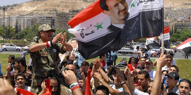 June 20: Pro-Syrian regime protesters shout President Bashar Assad slogans after he delivered a speech, in Damascus, Syria.