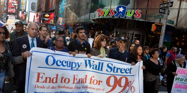 FILE – Demonstrators affiliated with the Occupy Wall Street protests walk through Times Square during an 11-mile march from uptown Manhattan to Zuccotti Park, Monday, Nov. 7, 2011, in New York. Elected officials, labor leaders and other protesters started walking in Washington Heights to show solidarity with the Occupy Wall Street movement. (AP Photo/John Minchillo)