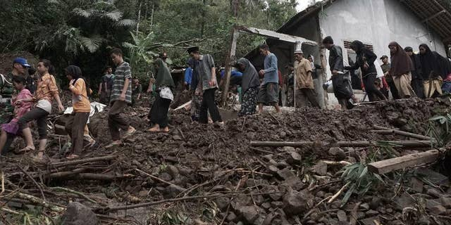 Villagers walk through an area wrecked by landslides in Banjarnegara, Central Java, Indonesia.