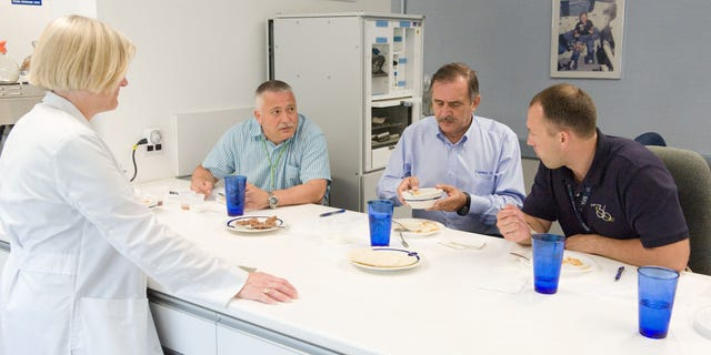 PHOTO DATE: 01 August 2012LOCATION: Bldg. 17 - JSC Food LabSUBJECT: Expedition 35/36 Russian cosmonauts during food tasting in JSC Food Lab. Vinogradov, Yurchikin and Misurkin with Russian interpreter. PHOTOGRAPHER: Mark Sowa
