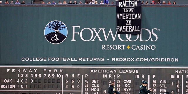 A banner is unfurled over the left field wall during the fourth inning of a baseball game between the Boston Red Sox and the Oakland Athletics.