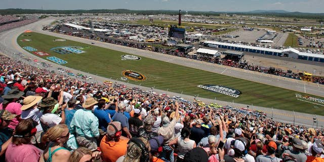 Casey Mears (13) and Ricky Stenhouse Jr. (17) crash on the final lap while Clint Bowyer (15) spins past them during the Talladega 500 NASCAR Sprint Cup Series auto race at Talladega Superspeedway, Sunday, May 3, 2015, in Talladega, Ala. (AP Photo/Butch Dill)