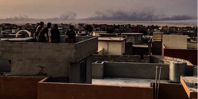 Black smoke from burning tires rises in the distance as Peshmerga fighters keep watch from a post outside Mosul.