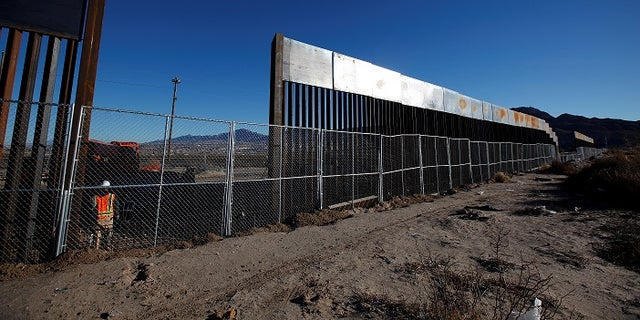 A worker stands next to a newly built section of the U.S.-Mexico border fence opposite Mexican city of Ciudad Juarez.