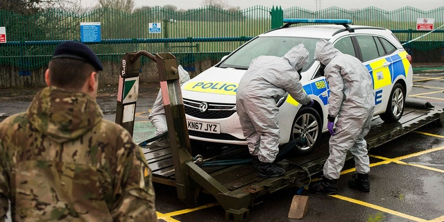In this image dated Friday March 9, 2018, and issued Saturday March 10, 2018, by Britain's Ministry of Defence, showing troops in protective gear as they work to remove a contaminated police car from the Accident and Emergency entrance at the District Hospital in Salisbury, England.