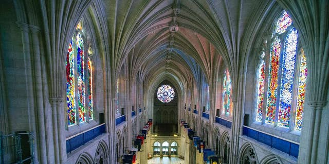 """FILE - This Wednesday, Feb. 18, 2015 file photo shows the nave of the Washington National Cathedral in Washington. A day after Donald Trump is sworn in, he and his cabinet members plan to attend a prayer service at the cathedral where """"all faiths will be represented at his request,"""" according to the Washington Episcopal bishop who oversees the cathedral. But the customary ceremony is complicated this time by anger over the president-elect's rhetoric on Muslims, immigrants and others. (AP Photo/Cliff Owen)"""