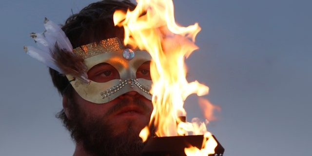 A participant takes part in a fire ceremony as approximately 70,000 people from all over the world gathered for the annual Burning Man arts and music festival in the Black Rock Desert of Nevada in 2017.