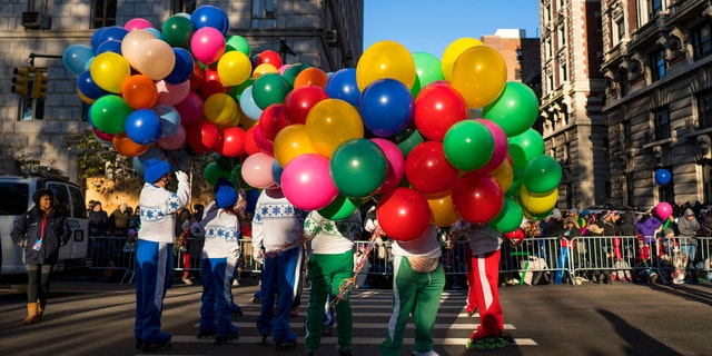 Participants take their place along the parade route before the Macy's Thanksgiving Day Parade begins in New York, Thursday, Nov. 23, 2017.